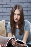 Young female reading magazine Royalty Free Stock Photography