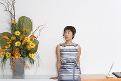 Young female receptionist by desk looking at flower arrangement Royalty Free Stock Images