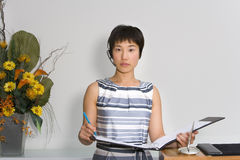 Young female receptionist with folder by flower arrangement, portrait Royalty Free Stock Image