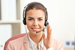 Young female receptionist wearing headphones. In office royalty free stock photography