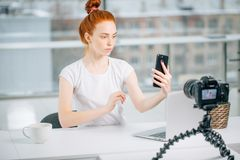 Young female redhead blogger with laptop recording video at home and take selfie.  Stock Photography