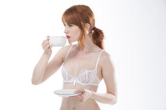 Young female redhead holding cup and saucer Royalty Free Stock Photos