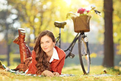 Young female relaxing on a grass with bicycle in park Stock Images