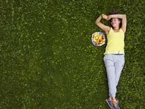Young female relaxing on the grass. Next to the fruit plate, overhead image stock photo