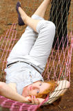Young female relaxing in hammock. Beautiful red-haired female relaxing in a hammock, looking into the camera Royalty Free Stock Images
