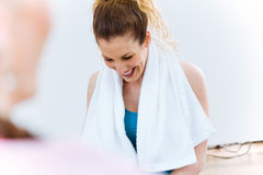 Young female relaxing on yoga mat and talking after workout session. stock image