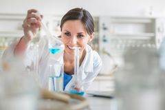 Young, female researcher in a lab. Young, female researcher carrying out experiments in a lab shallow DOF; color toned image Stock Photo