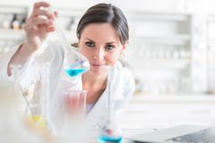 Young, female researcher in a lab. Young, female researcher carrying out experiments in a lab shallow DOF; color toned image Stock Photos