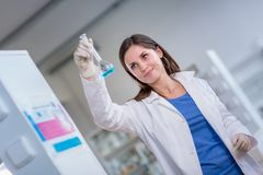 Young, female researcher in a lab. Young, female researcher carrying out experiments in a lab shallow DOF; color toned image Royalty Free Stock Images