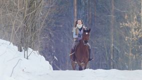 Young female rider riding a black horse through the drifts in the winter frozen forest stock photos