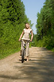 Young female riding a bike in nature Stock Photography