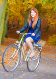 Young female is riding bike in the park. Stock Photography