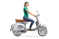Young female riding a vintage scooter royalty free stock photo