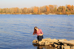 Young female by the river in autumn Royalty Free Stock Image