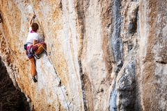 Young female rock climber on a cliff. Face Stock Photo