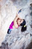 Young female rock climber on a cliff Stock Photos