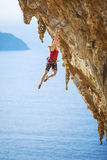 Young female rock climber on a cliff. Royalty Free Stock Image