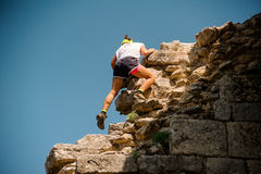 Young female rock climber climbing challenging route. No face Stock Image