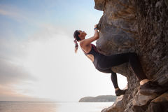 Young female rock climber climbing challenging route on overhanging cliff Stock Photos