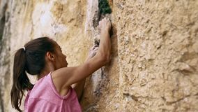 Young female rock climber trying to climb on a cliff, searching, reaching and gripping hold.