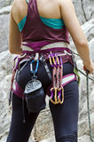Young female rock climber. Wearing safety harness with climbing tools,preparation for the climb Stock Photo