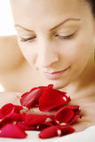 Young female with rose petals. Beautiful retouched woman enjoying a bunch of rose-petals royalty free stock images