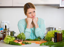 Young female with rotten vegetables at home Royalty Free Stock Photography