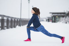 Young female runner doing flexibility exercise for legs before run at snow winter promenade, horizontal. Telephoto stock images