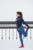 Young female runner doing flexibility exercise for legs before run at snow winter promenade, vertical. Telephoto stock photo