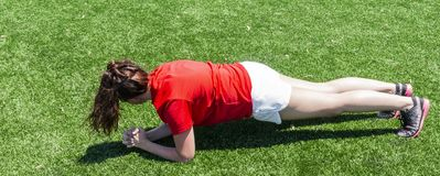 Young female runner doing a plank for core work royalty free stock photo