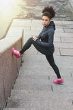Young female runner doing stretching legs. On stairs stock photos