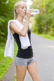 Young female runner drinking water after workout Royalty Free Stock Image