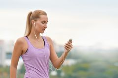 Young female runner is having break and listening to music during the run royalty free stock photography