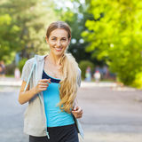 Young female runner in hoody is jogging in the city Stock Photos