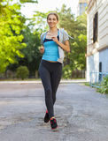 Young female runner in hoody is jogging in the city Royalty Free Stock Photo