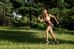 Young female runner jogging during outdoor workout in a park. Beautiful fit girl. Weight Loss. Sport LIfestyle. royalty free stock photos