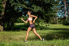 Young female runner jogging during outdoor workout in a park. Beautiful fit girl. Weight Loss. Sport LIfestyle. stock photography