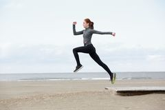Young female runner jumping outdoors Stock Images