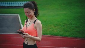 Young female runner listening music with headphones outdoor after sport exercise
