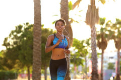 Young female runner listening to music on headphones Stock Photography