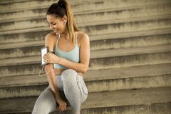 Young female runner resting on stirs. Portrait of pretty young female runner resting on stairs Stock Photography