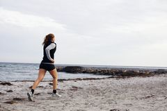 Young female runner running on beach Stock Photos