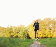 Young female runner running outside in park. Fitness model in sports clothing jogging outdoors. Health and fitness exercise concept. Caucasian young woman Royalty Free Stock Image