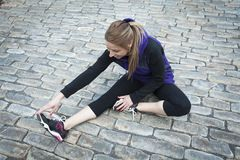 Young female runner sitting on tiled pavement in Royalty Free Stock Images