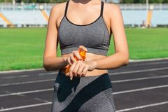 Young female runner standing and putting sun lotion on hand. Girl using sunscream before sport running exercise on summer morning royalty free stock photo