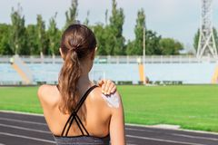 Young female runner standing and putting sun lotion on hand. Girl using sunscream before sport running exercise on summer morning stock image
