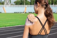 Young female runner standing and putting sun lotion on hand. Girl using sunscream before sport running exercise on summer morning royalty free stock images