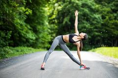 Young female runner stretching arms before running. Woman warming before workout in the park stock images