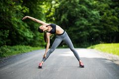 Young female runner stretching arms before running. Woman warming before workout in the park stock photo