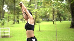 Young female runner stretching muscles in nature park